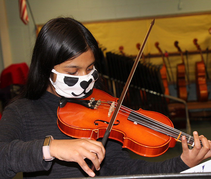 Guilderland Elementary student with long dark hair playing violin wearing a panda mask
