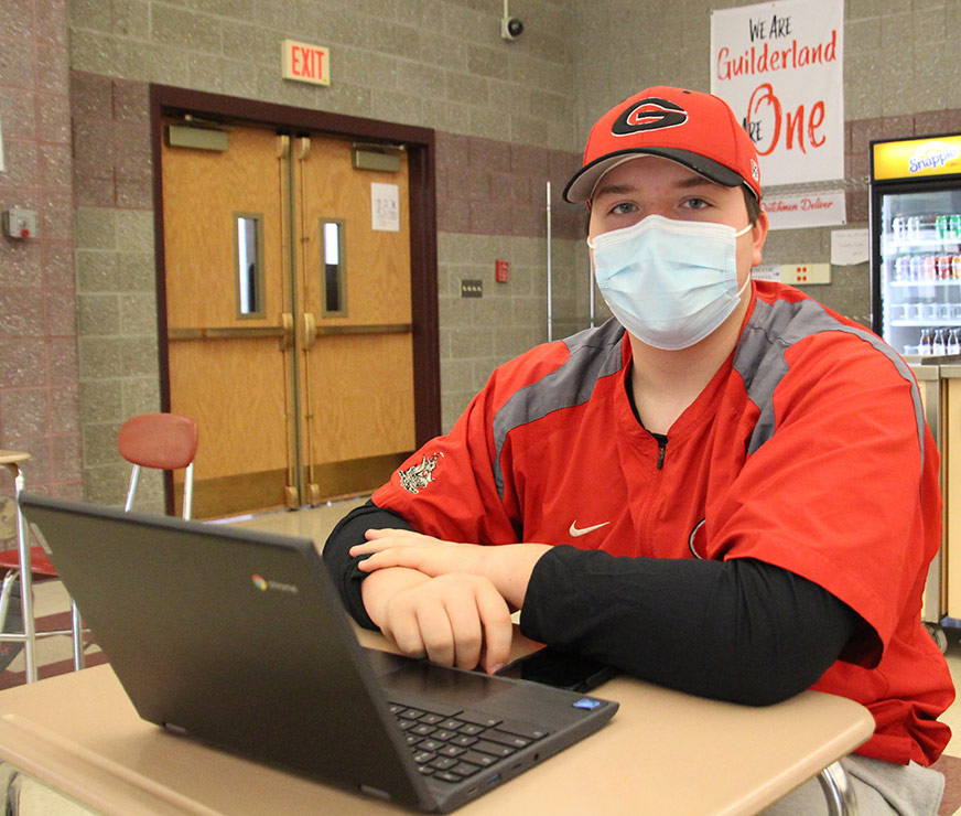 Guilderland High school student wearing aGuilderland jersey and hat sitting at a laptop with a mask on.