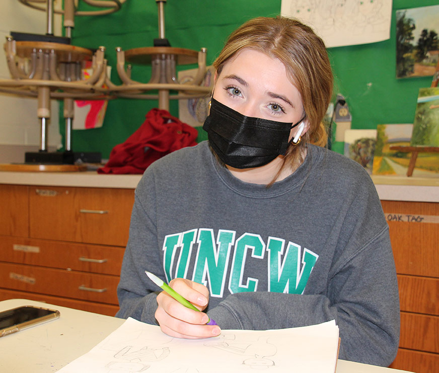 Guilderland High School student wearing a mask sitting in art classroom drawing
