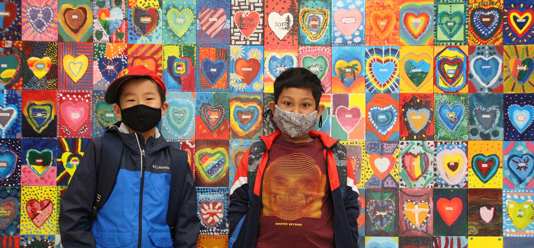 Two Guilderland students wearing masks stand in front of a large background of multi-colored and patterned hearts