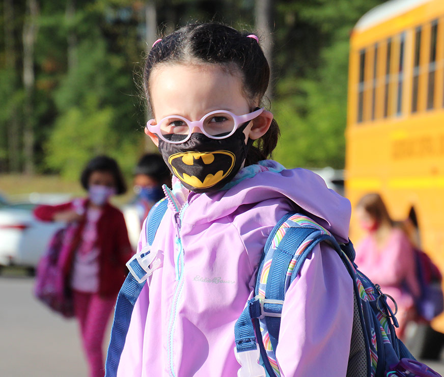 Pine Bush Elementary student getting off school bus wearing pink glasses and a batman mask