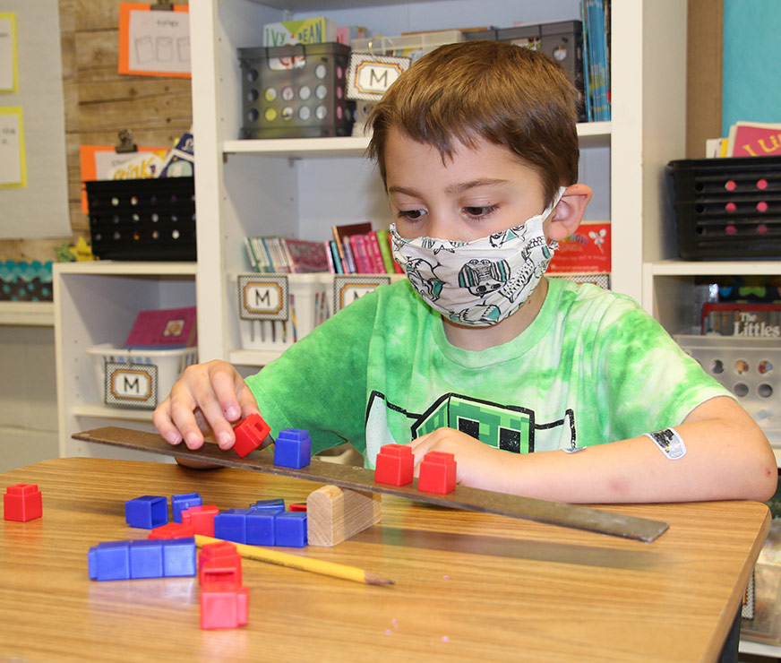 Westmere Elementary student sitiing at a desk balancing small plastic blocks on a wood lever device