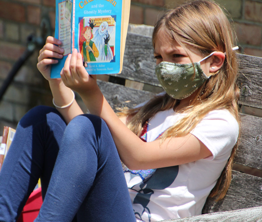 Westmere Elementary student wearing a mask, sitting in the sun on a bench reading a book